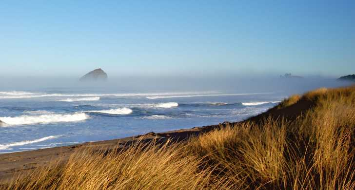 Haystack Rock at Pacific City peaks over the fog