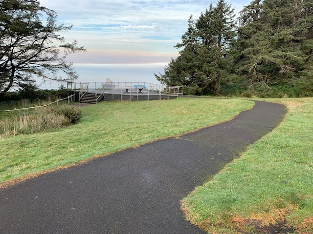 Cape Meares Day use area - paved path to accessible viewing deck overlooking Pacific Ocean. Viewing deck offers bench and interpretive panels.