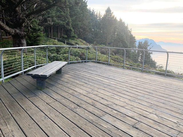 Cape Meares Day use area - paved path to accessible viewing deck overlooking Pacific Ocean. Bench available for seating.