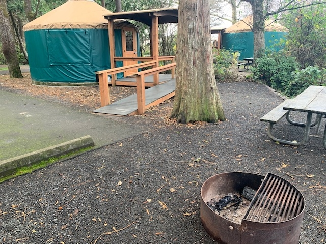 Yurt with accessible ramp. Access to fire pit and picnic table on compact natural surface.